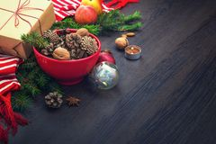 Christmas decoration - red bowl full of fir-cones, gift box wrapped in kraft paper, pine branches, candle, nuts, anise, apples, ch Royalty Free Stock Photos