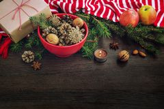 Christmas decoration - red bowl full of fir-cones, gift box wrapped in kraft paper, pine branches, candle, nuts, anise, apples and stock photo
