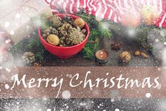 Christmas decoration - red bowl full of fir-cones, gift box wrapped in kraft paper, pine branches, candle, nuts, anise, apples and stock photos