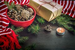 Christmas decoration - red bowl full of fir-cones, gift box wrapped in kraft paper, pine branches, candle and red and white stripe stock image