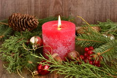 Christmas decoration with red candle burning Royalty Free Stock Image