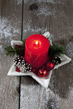 Christmas decoration, red candle, fir twig, Christmas sphere on wooden background Royalty Free Stock Photo