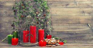 Christmas decoration with red candles, birdcage and pine branch. Cinnamon cookies, nuts and spieces. vintage home interior. retro style toned picture Stock Photos
