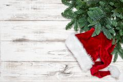 Christmas decoration red hat green pine tree branches. Christmas decoration red hat with green pine tree branches on bright wooden background royalty free stock images
