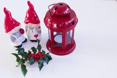 Christmas decoration with red lantern and holly. Porcelain Figurines,very charming boy and girl elves ,  on white backgrou. Nd,empty space in your text Royalty Free Stock Image