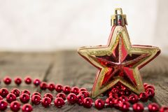 Christmas decorations, golden and red. Christmas decoration with red pearls and red glossy star on a wooden surface Royalty Free Stock Photos