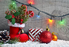Christmas decoration:red Santa`s boot,fir tree,garland,gift,pine cone and toys on wooden background.Christmas background. Stock Images