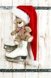 Christmas decoration. Red Santas hat, Teddy Bear, ice skates Stock Photos