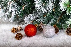 Christmas decoration red and silver balls in a tree with tinsel and pinecone in snow. Christmas decoration, red and silver balls in a snowed tree with pinecones stock images