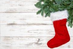 Christmas decoration red sock green pine tree branches. Christmas decoration red sock with green pine tree branches on bright wooden background royalty free stock photo