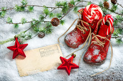 Christmas decoration red stars antique baby shoes postcard. Christmas decoration red stars, sweets and antique baby shoes on snow background. Empty postcard for Royalty Free Stock Photography