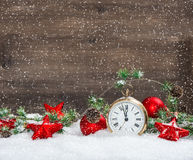Christmas decoration red stars and antique golden clock. Vintage christmas decoration red stars and antique golden clock in snow over wooden background Royalty Free Stock Photo