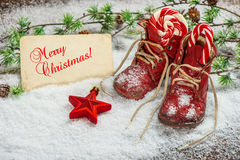 Christmas decoration red stars, sweets and antique baby shoes Royalty Free Stock Photos