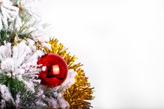 Christmas decoration red and silver balls in a tree with tinsel and pinecone in snow. Christmas decoration, red tinsel with a silver ball in a snowed table and royalty free stock photo