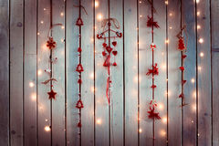 Christmas decoration with red and white colours with shapes of hearts, angels and deers hanging on a white wooden texture wall. Stock Images