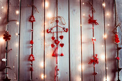 Christmas decoration with red and white colours with shapes of hearts, angels and deers hanging on a white wooden texture wall. Royalty Free Stock Photo