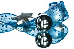 Christmas decoration with reflection. Christmas silver balls and star wrapped with blue ribbon Stock Photography