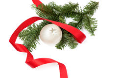Christmas decoration with ribbon and white Christmas ball. Christmas decoration with pine branch, white Chrismas ball decorated with a star and a red, curled Stock Photography