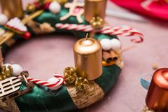 Christmas decoration round wreath golden colors with candles, creating process with hands and hot glue. Christmas decoration round wreath, shiny accessories royalty free stock photography