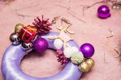 Christmas decoration round wreath golden colors with candles, creating process with hands and hot glue. Christmas decoration round wreath, shiny accessories stock images