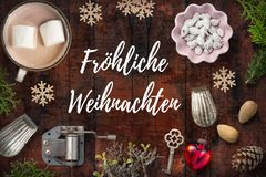 Christmas decoration on rustic wooden background and the German message for `Merry Christmas`. Christmas decoration and sweets on rustic wooden background and Stock Image