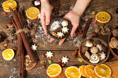 Christmas decoration on a rustic wooden table. Female hands with christmas decoration on a rustic wooden table Royalty Free Stock Image