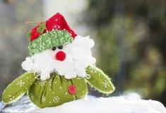 Christmas decoration with Santa Claus figurine in the snow. Christmas decoration with closeup on green Santa Claus figurine in the snow Stock Photos
