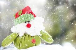 Christmas decoration with Santa Claus figurine in the snow. Christmas decoration with closeup on green Santa Claus figurine in the snow Royalty Free Stock Image
