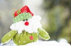 Christmas decoration with Santa Claus figurine in the snow. Christmas decoration with closeup on green Santa Claus figurine in the snow Royalty Free Stock Photo