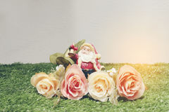 Christmas decoration of Santa Claus with flowers on green grass Stock Photo