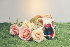 Christmas decoration of Santa Claus with flowers on green grass Royalty Free Stock Images