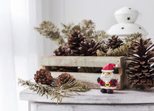 Christmas decoration of santa claus and pine cones on wooden cab Royalty Free Stock Images