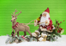 Christmas decoration: Santa Claus with sledge and reindeer. On green background santa with his roe and stag on snow Royalty Free Stock Photos