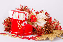 Christmas decoration. With Santa's red boot, garland, beads  on gray background Stock Image