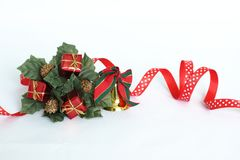 Christmas decoration in the shape of a fir tree crown on a white background with a red ribbon, a golden bell, green leaves and red Stock Image