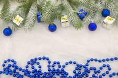 New Year`s decorations, blue, green, silver and white. Christmas decoration with shiny blue balls, packets and green branches of Christmas tree on a white Royalty Free Stock Photography