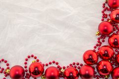 New Year`s decorations, bright red and white. Christmas decoration with shiny red balls and red beads on a white base Stock Photo