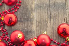 Christmas decoration, red and rustic. Christmas decoration with shiny red balls and red beads on a wooden base Royalty Free Stock Photos