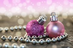 Christmas decorations, silver and pink. Christmas decoration with silver beads and pink shiny balls on a wooden base with bokeh background Royalty Free Stock Photo