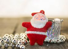 Christmas decorations, silver and red. Christmas decoration with silver beads, silver shiny drum and Santa Claus on a wooden base Stock Photo