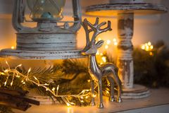 Christmas Decoration silver figure of a deer, cinnamon sticks in festive lights garland yellow. royalty free stock photography