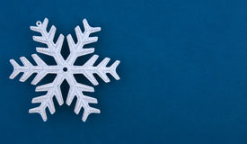 Christmas decoration silver snowflake. On blue textured paper background. Useful for any type of Christmas card Royalty Free Stock Image