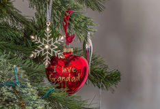 Christmas decoration silver star and `I love Grandad` red heart bobble in behind. Set on a decorated christmas tree is a silver star and a heart shaped pendant Royalty Free Stock Photography
