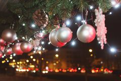 Christmas decoration with a silver toy in the form of balls on the blurry background of night city lights. Christmas decoration with a silver toy in the form of royalty free stock images