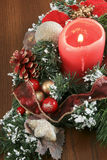 Christmas Decoration sitting on a Brown Table. A Christmas decoration with green boughs covered with snow and red balls, In the centre is a lighted red candle Royalty Free Stock Photography