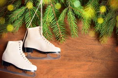 Christmas decoration. Skates and fir branch on wooden background. Stock Image