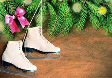 Christmas decoration. Skates and fir branch on wooden background. Royalty Free Stock Photo