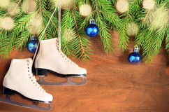 Christmas decoration. Skates and fir branch on wooden background. Royalty Free Stock Photography