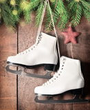 Christmas decoration. Skates and fir branch on wooden background. Stock Images