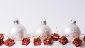 Christmas decoration on snow. Christmas glass balls and presents on snow Stock Photography